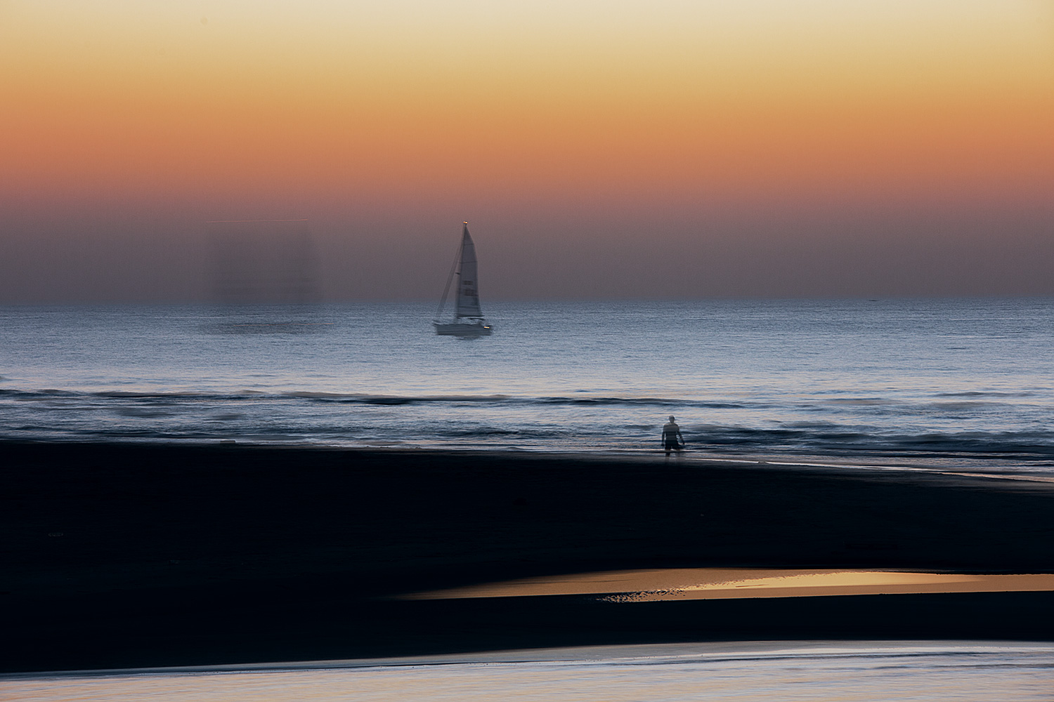 A Man and a Sailboat After Sunset